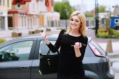 Elegant gekleidete Dame, die nahes Auto steht und Autoschlüssel hält Lizenzfreie Stockfotos