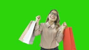 Elegant gekleidete schöne junge Frau mit den Gläsern, die Einkaufstaschen in beiden Händen enthusiastisch lächelnd halten und stock video