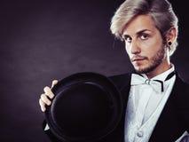 Elegant gekleideter Mann, der schwarzen Fedorahut hält Stockfotografie