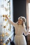 Elegant gekleidetes Mädchen von 8-9 Jahren mit Freude berührt Goldweihnachtsgirlanden Stockbild