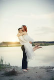 Elegant gentle stylish groom and bride near river or lake. Wedding couple in love Stock Photography