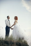 Elegant gentle stylish groom and bride near river or lake. Wedding couple in love Royalty Free Stock Photos