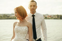Elegant gentle stylish groom and bride near river or lake. Wedding couple in love Stock Photos