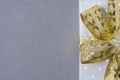 Elegant Gift Box Wrapped in Grey Silver Paper with Polka Dots Golden Ribbon Bow. Christmas New Years Valentine Presents Shopping Royalty Free Stock Photo