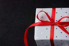 Elegant Gift Box Wrapped in Grey Silver Paper with Polka Dots Red Ribbon on Black Background. Christmas New Years Valentine Stock Photos