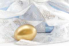 Elegant gift of gold nest egg with silver ribbon Stock Images