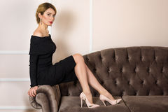 Elegant Girl on a couch in a Black Classic style dress portrait Stock Image
