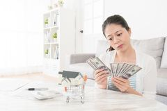 Elegant girl counting savings money in living room. Young elegant girl counting savings money in living room feeling sadness because she planning buying new Stock Photo