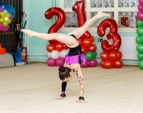 Elegant girl doing crafty splits on art gymnastics competitions. Indoors Stock Photos