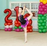 Elegant girl doing crafty trick on gymnastics performance. Indoors Stock Photo