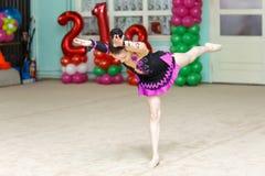 Elegant girl doing crafty trick on gymnastics performance. Indoors Stock Images