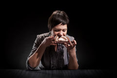 Elegant girl eating a chocolate cake. Young elegant woman eating a chocolate cake Stock Images