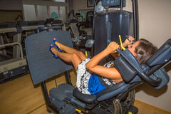 Leg press woman. Attractive young woman with heels and evening dress in blue and white, exercising in the gym on a bench press Royalty Free Stock Image