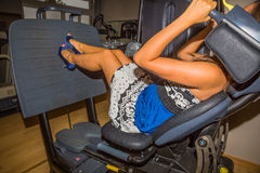 Leg press. Attractive young woman with heels and evening dress in blue and white, training in the gym on a bench press Stock Photos