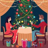 Girl and guy toast glasses in the Christmas Eve. Elegant girl and guy sitting at the table with raised glasses in the Christmas Eve. Near Christmas tree and gift Stock Photography