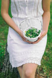 Elegant girl holding small white basket full of spring flowers Royalty Free Stock Photography