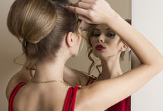 Elegant girl looking in the mirror Royalty Free Stock Photography
