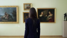 Elegant girl looks at the pictures in the museum of modern art. paintings in gallery during art exposition. Young woman. Watching works of art paintings on the stock video footage