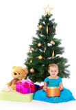 Elegant girl near the Christmas tree. Cute little girl sitting on the floor at the beautifully narazeni Christmas tree. In the hands of the girls round box with Stock Image