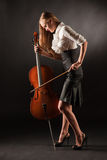 Elegant girl playing with passion on bass-viol. Studio shot Stock Photo