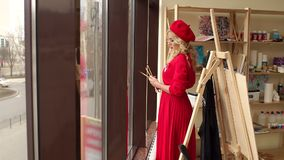 Portrait of a beautiful girl in a drawing school among easels and paintings. An elegant girl in a red dress and a red beret stands near a large window in the stock video footage