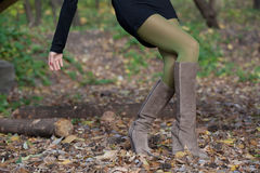 Elegant girl in suede boots walking in the woods Royalty Free Stock Images