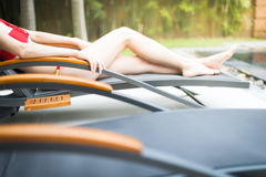 Elegant girl in swimsuit lying on sun lounger. Royalty Free Stock Photography