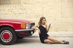 Elegant girl using a smartphone next to a car. Elegant girl using a smartphone next to a red car Royalty Free Stock Photos