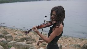 Elegant girl with violin. Brunette violinist in dress plays at sea background stock footage