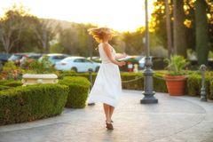 Elegant girl in a white dress dancing carelessly in a sunset city street. Stunning young woman Royalty Free Stock Image