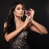 Elegant glamourkvinna i en härlig klänning med doft på mörk bakgrund royaltyfri foto