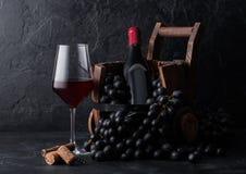 Elegant glas rode wijn met donkere druiven en fles wijn binnen uitstekend houten vat op zwarte steenachtergrond naughty royalty-vrije stock afbeelding