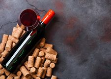 Elegant glass and bottle of red wine with corks on stone kitchen table background. Top view. Space for text royalty free stock images