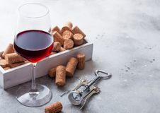 Elegant glass of red wine with box of corks and opener on stone kitchen table background stock images
