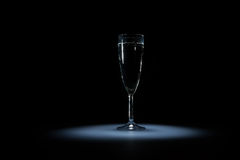 Elegant glass of water with bubbles on the black background on light spot Royalty Free Stock Photos