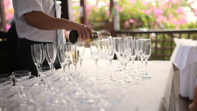 Elegant glasses with champagne standing in a row on serving table during the celebration. Waiters pouring champagne stock video