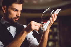 Elegant glory of red drink. Wineglass with scarlet nectar against napkin in hands of sommelier Stock Photo