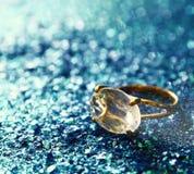 elegant gold diamond ring on blue glitter background Stock Image