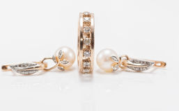 Elegant gold earrings with pearls and a chunky ring with small d Royalty Free Stock Images