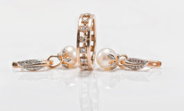 Elegant gold earrings with pearls and a chunky ring with small d Royalty Free Stock Photography