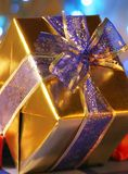 Elegant gold present with blue ribbon Stock Photography