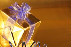 Elegant gold present with blue ribbon Royalty Free Stock Image