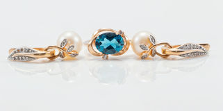 Elegant gold ring with Topaz and gold earrings with natural pear Stock Image