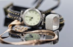 Elegant gold and silver ring and chain lie on the background of. Women`s watches with leather strap Stock Image
