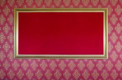 Elegant golden blank picture frame. On red textured wall background Stock Image