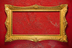 Elegant golden frame on red. Horizontal golden frame on red, grunge garage wall, inner and outer clipping paths included Royalty Free Stock Images