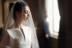 Elegant gorgeous bride gently looking under veil at stylish groo Royalty Free Stock Photography
