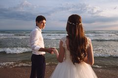 Elegant gorgeous bride and groom walking on ocean beach during sunset time. Romantic walk newlyweds on tropical island stock photos