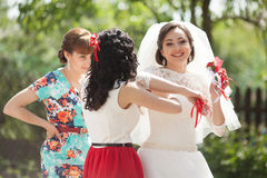 Elegant gorgeous brunette bride and bridesmaids with red boutonn Royalty Free Stock Photo