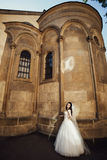 Elegant gorgeous happy bride standing on the background of a old Royalty Free Stock Photo
